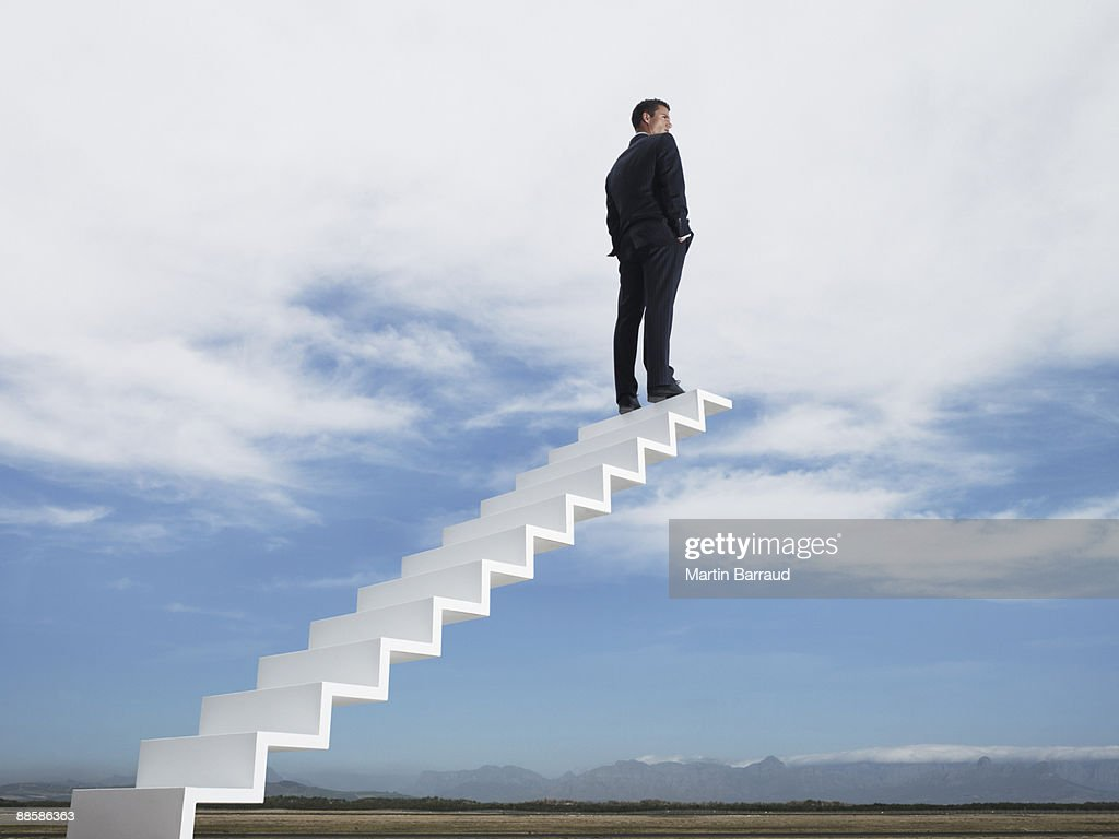 Businessman at end of stairway leading to the sky : Stock Photo