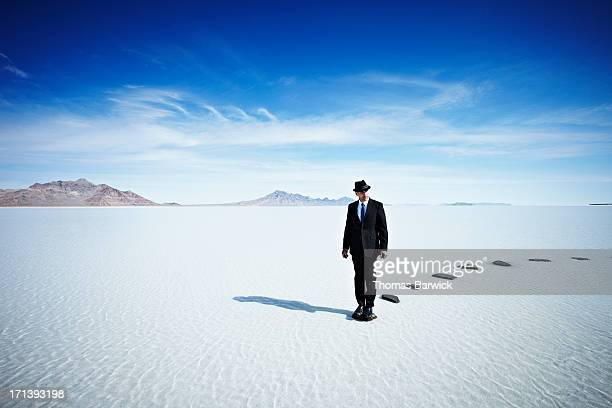 Businessman at end of stone pathway in lake