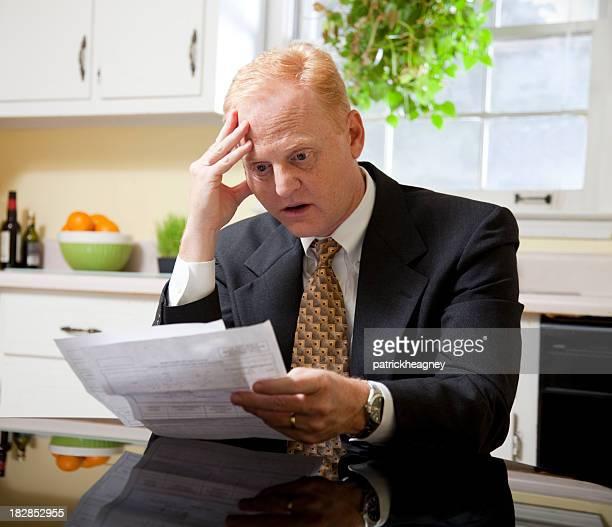 Geschäftsmann zu Hause mit Rechnungen