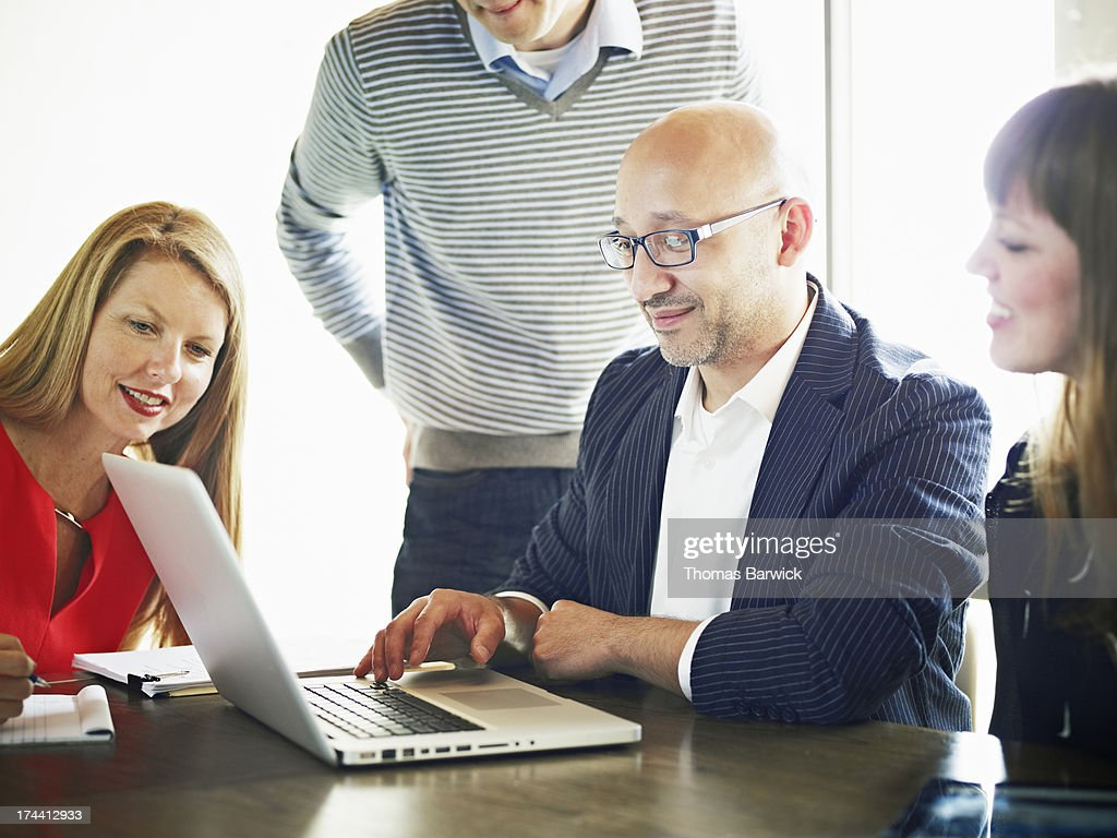 Businessman at laptop leading project discussion : Stock Photo