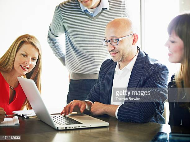 Businessman at laptop leading project discussion