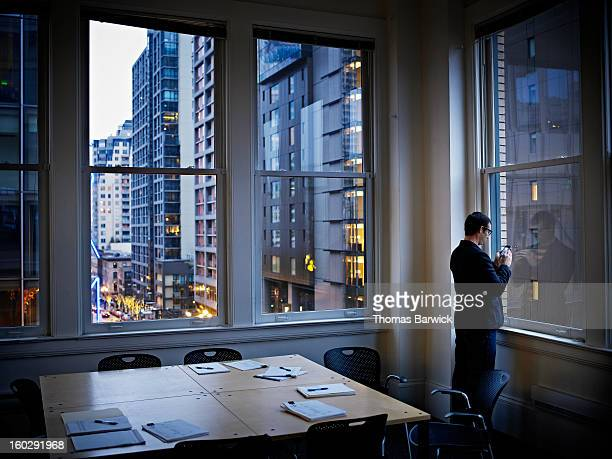 Businessman at office widow working on smart phone