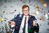 Happy businessman with bottle of champagne and two glasses standing under falling confetti
