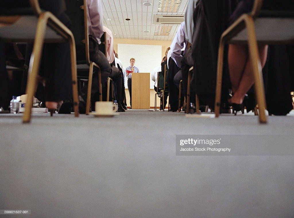 Businessman at podium addressing colleagues, ground view : Stock Photo