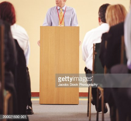 Businessman at podium addressing colleagues : Stock Photo