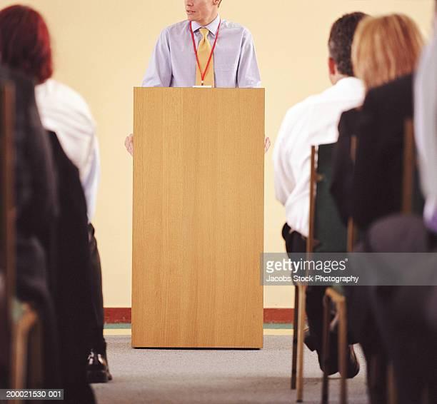 Businessman at podium addressing colleagues