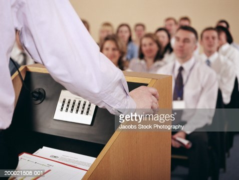 Businessman at podium addressing colleagues, rear view, close-up : Stock Photo