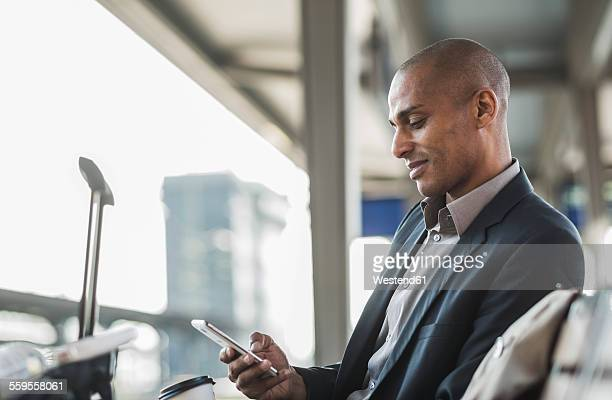 Businessman at the train station looking on smartphone