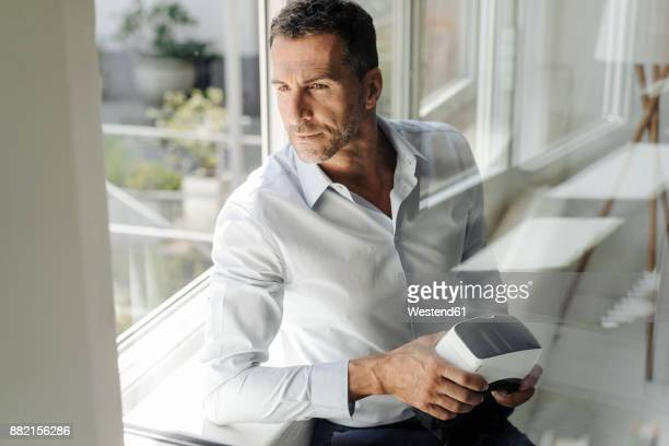 Businessman at the window holding VR glasses