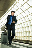 Businessman at train station looking at cell phone