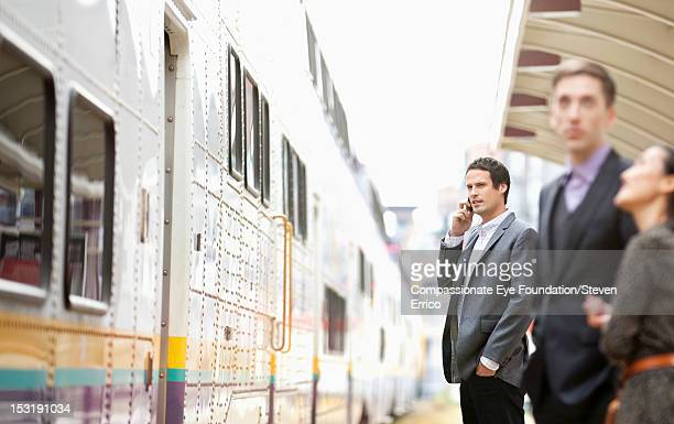 Businessman at train station using mobile phone