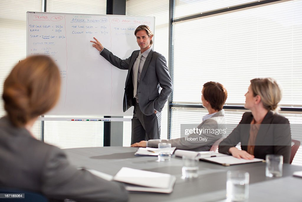Businessman at whiteboard presenting to co-workers : Stock Photo