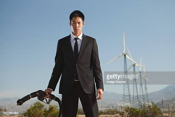 Businessman at wind farm with gas pump