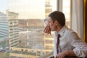Businessman at window deep in thought