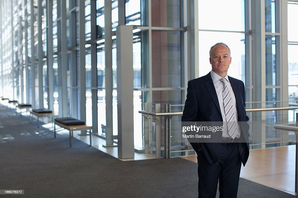 Businessman at window in office lobby : Stock Photo