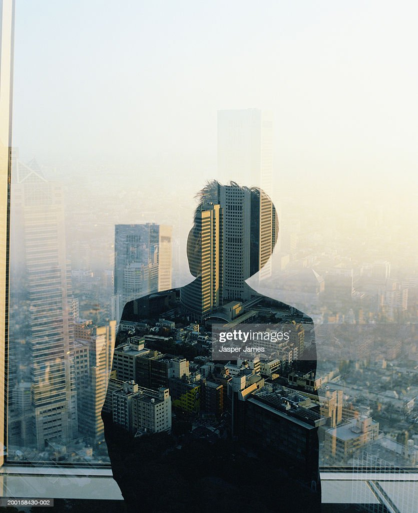Businessman at window overlooking cityscape (multiple exposure) : Stock Photo
