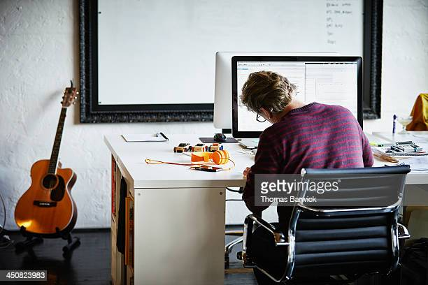Businessman at workstation writing on documents