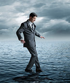 A businessman holds his arms out as he tentatively attempts to walk on water.