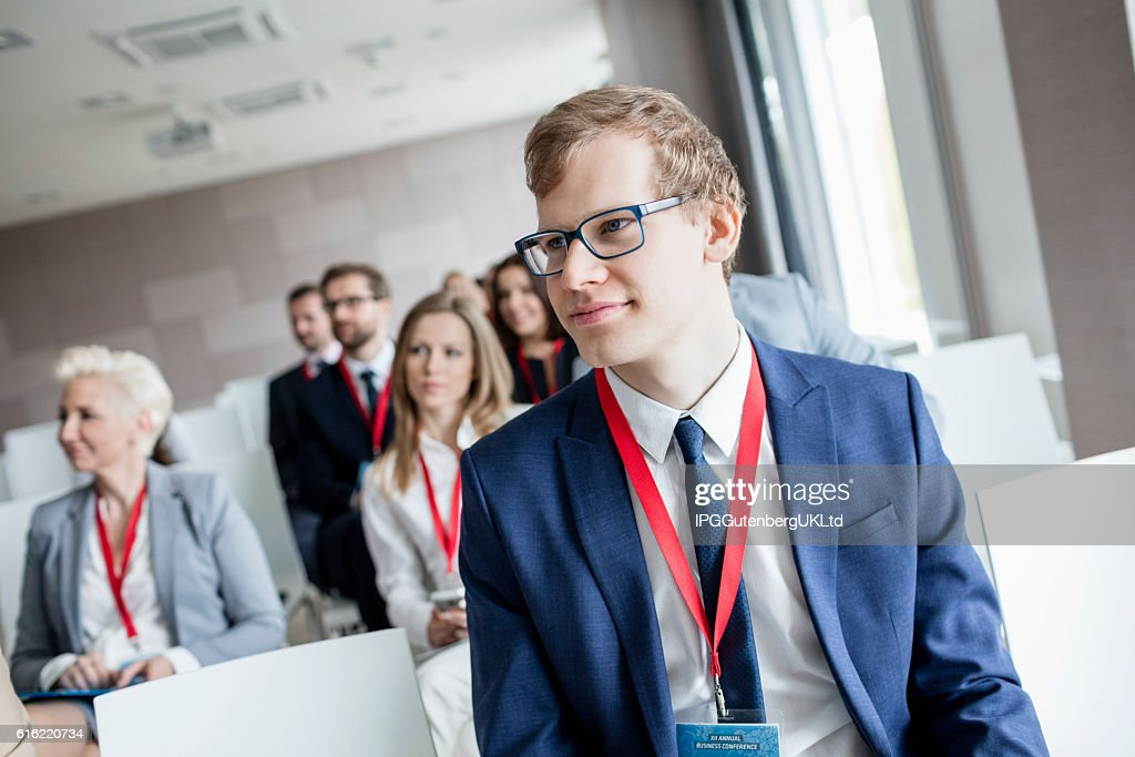 Businessman attending seminar in convention center : Photo