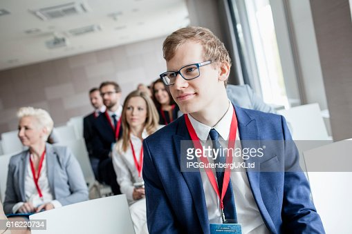 Businessman attending seminar in convention center : Stock Photo