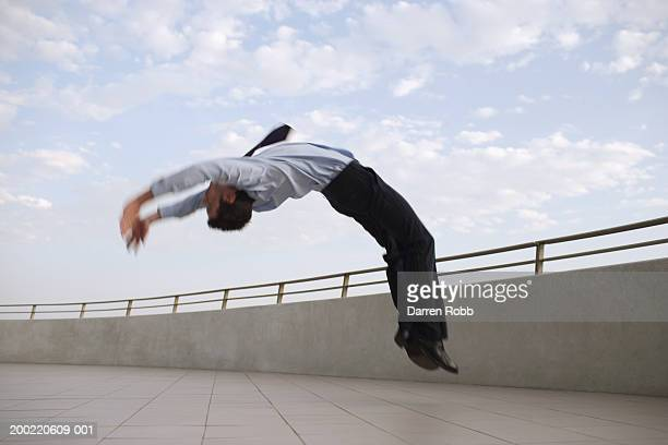 Businessman backflipping on balcony, side view (blurred motion)