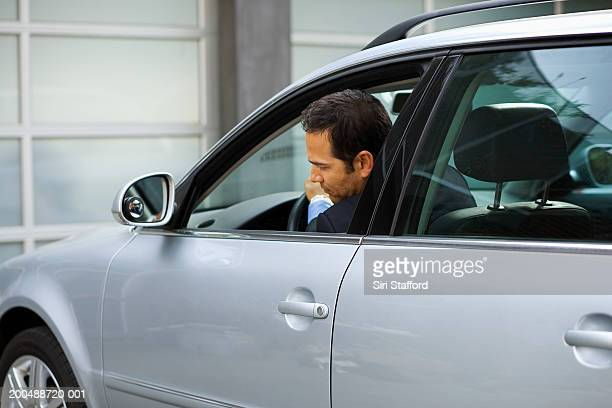 Businessman backing out car