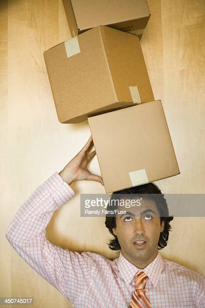 Businessman Balancing Boxes on Head