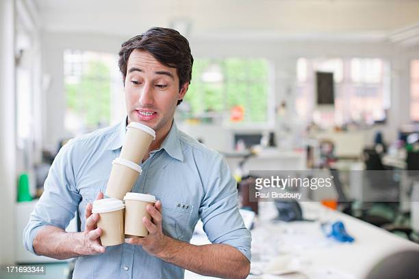 Businessman balancing coffee cups