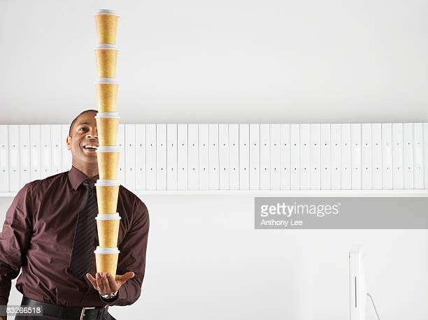 Businessman balancing large stack of paper coffee cups