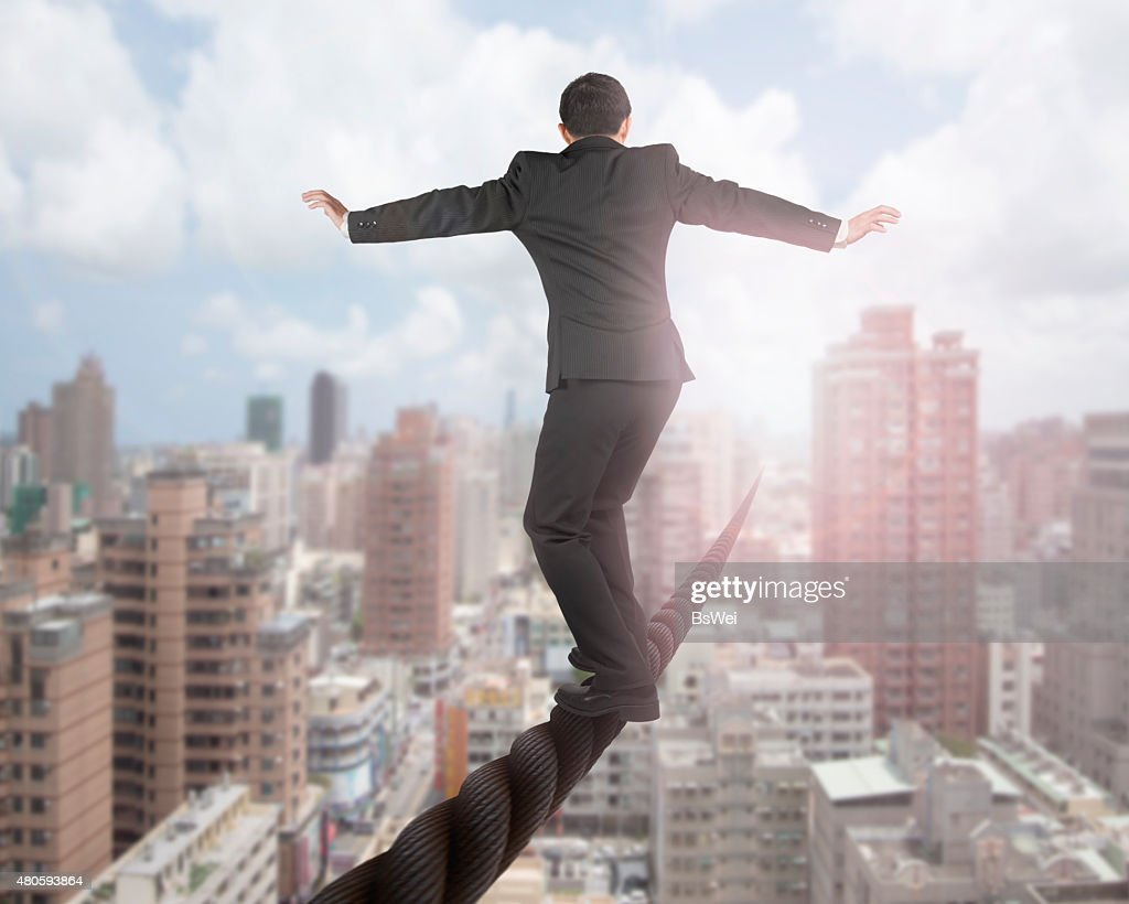 Businessman balancing on a wire with sky clouds cityscape : Stock Photo