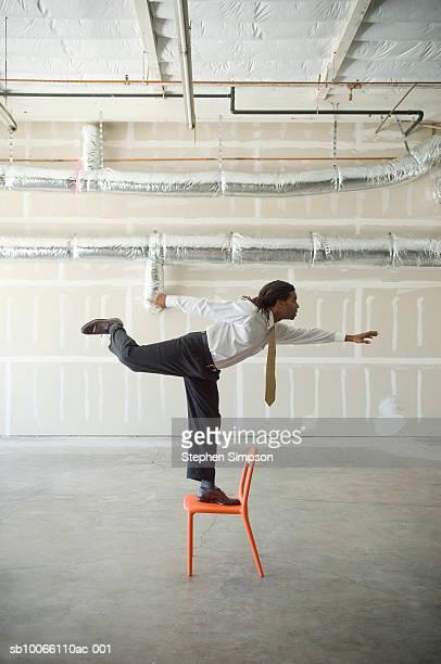 Businessman balancing on one leg on chair