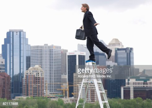 Businessman balancing on step ladder above city skyline