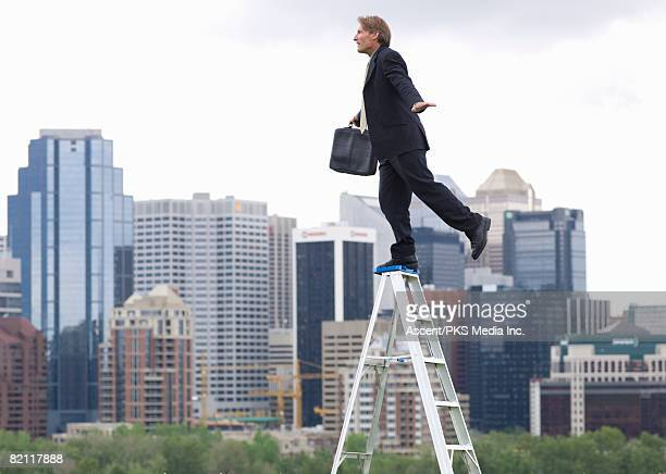 Businessman balancing on step ladder above city skyline