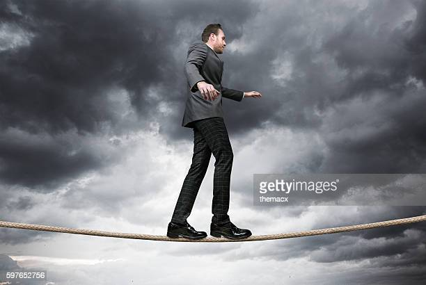 Businessman balancing on tightrope with stormy day
