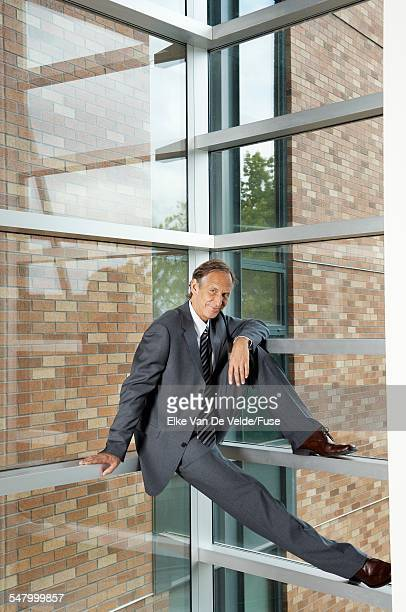 Businessman Balancing on Window Beams