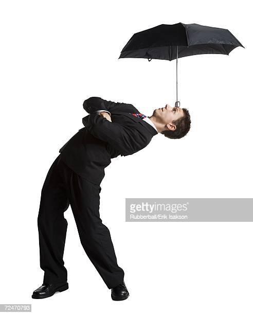Businessman balancing umbrella on his forehead
