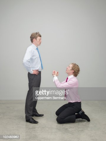 businessman begging on his knees : Stock Photo