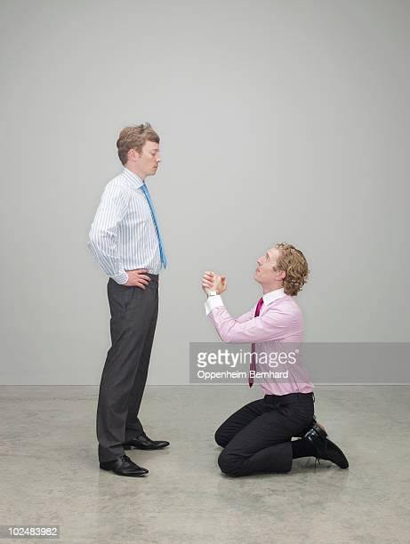 businessman begging on his knees