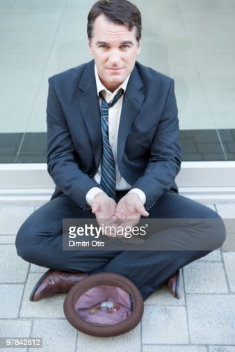 Businessman begging on pavement