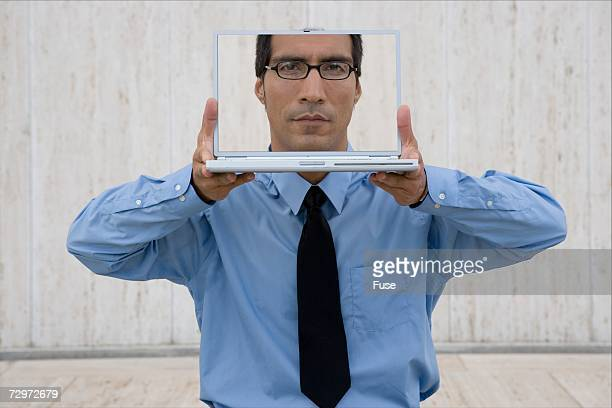 Businessman behind a laptop with his image