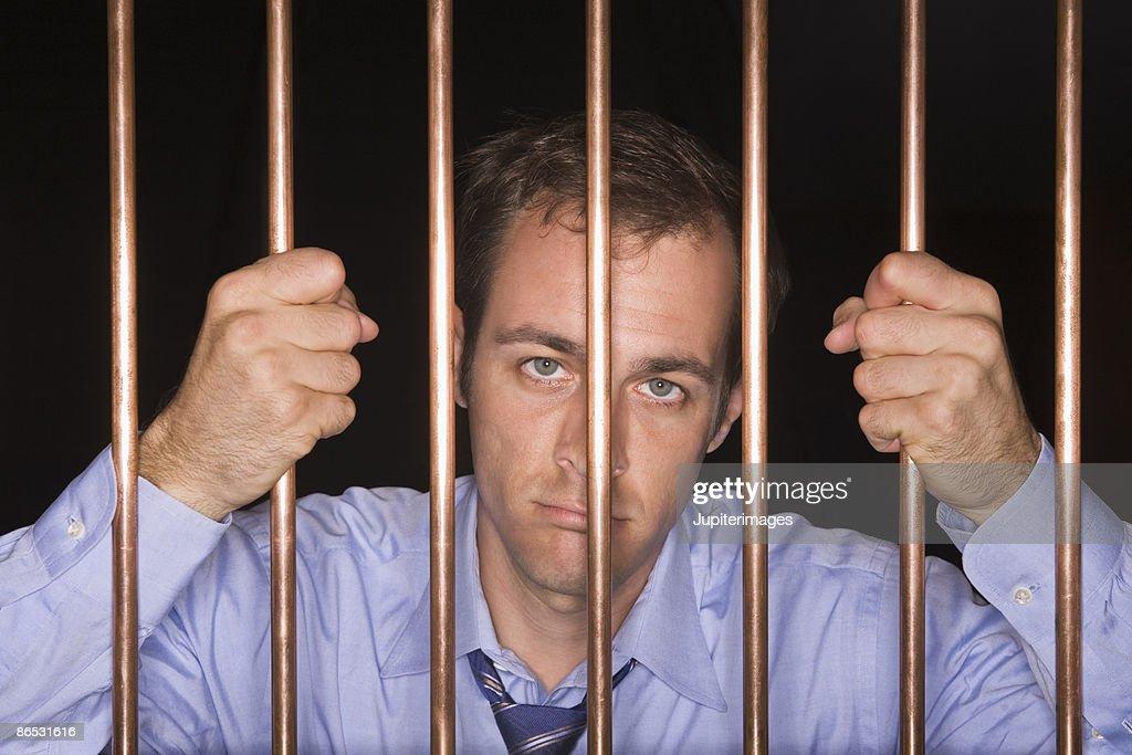 Businessman behind bars : Stock Photo