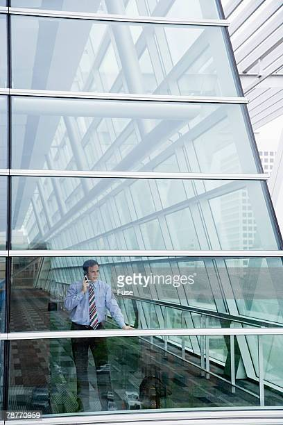 Businessman Behind Glass Facade on Cell Phone