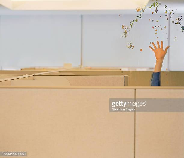 Businessman behind partition tossing confetti in office