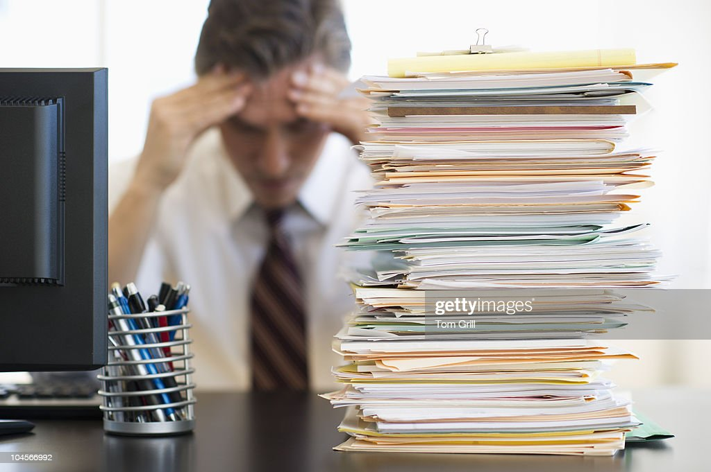 Businessman behind stack of paper : Stock Photo
