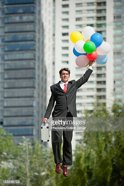 Businessman being carried away by bunch of balloons