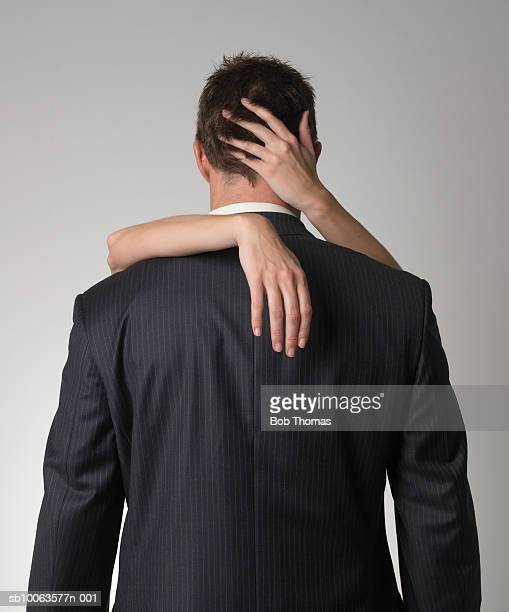 Businessman Being Embraced by Woman, Rear View