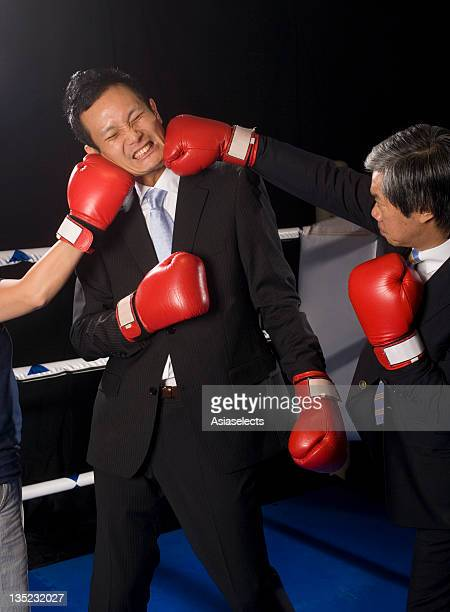 Businessman being hit by his two opponents in a boxing ring