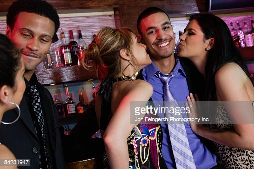 Businessman being kissed by two women in bar