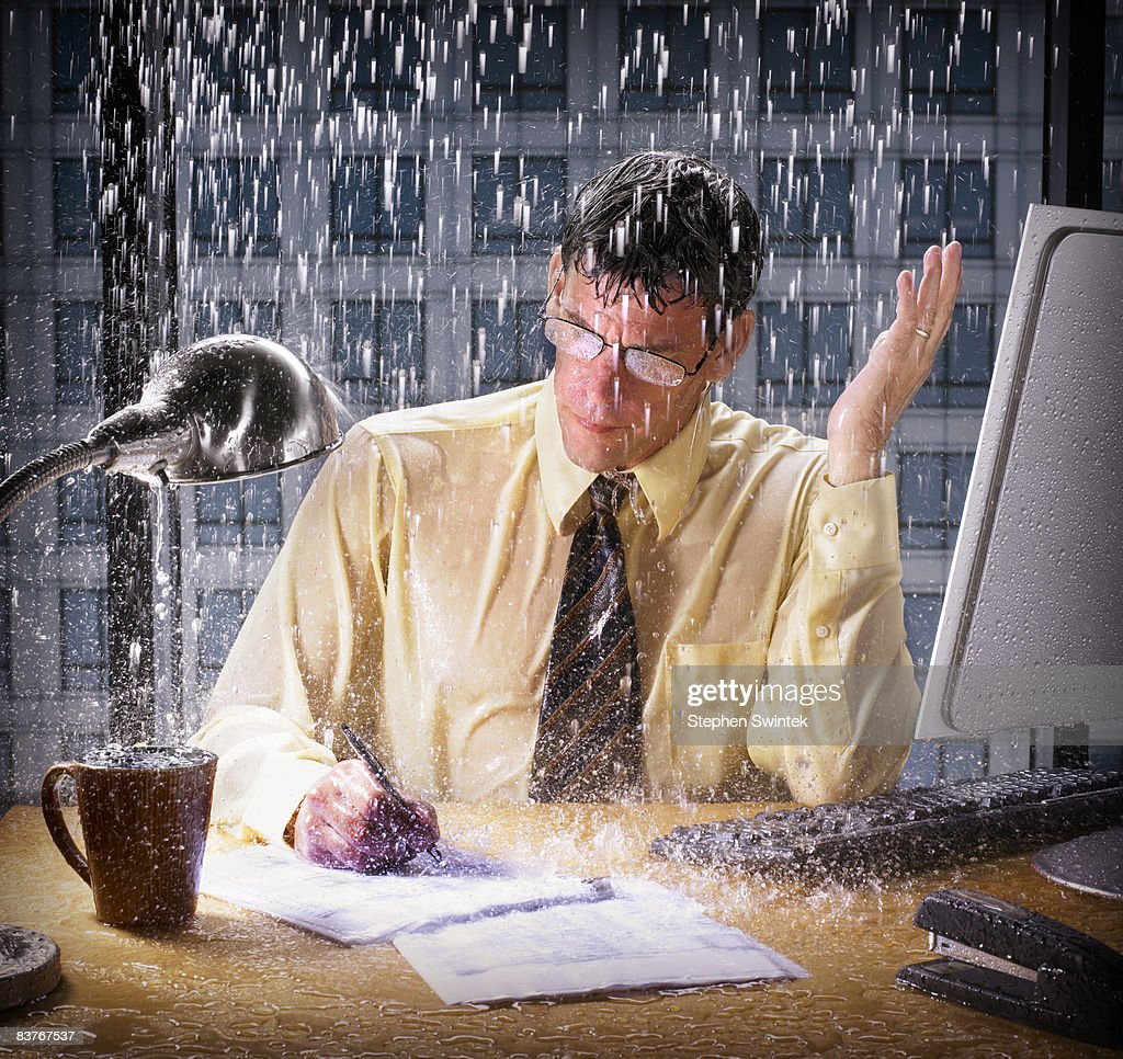 Businessman being rained on in his office