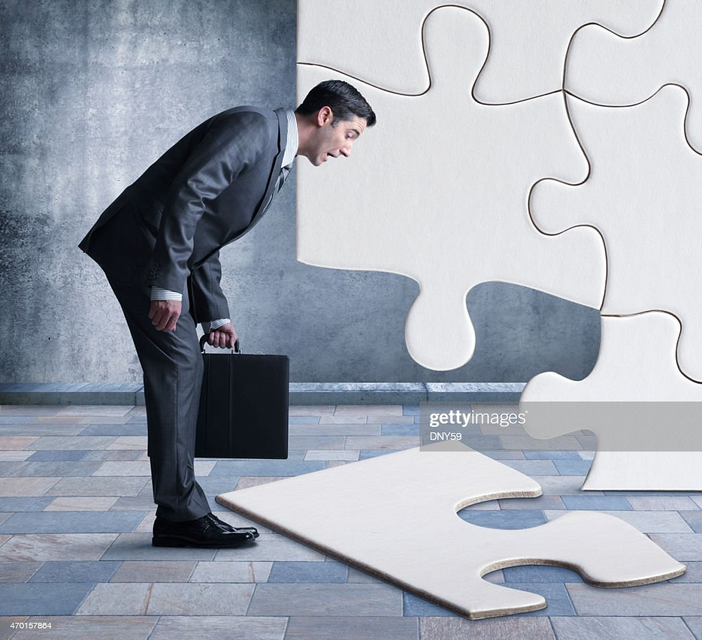 Businessman bent over looking at missing piece of puzzle